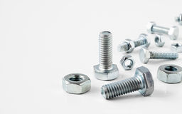 Close-up of various  metal steel nuts and bolts on white backgro Stock Photos