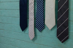 Close up of various neckties hanging by green wall Royalty Free Stock Photo