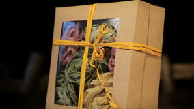 Close-up of various pasta in paper box rotates on black background. Assorted different kinds of pasta in a paper box stock video