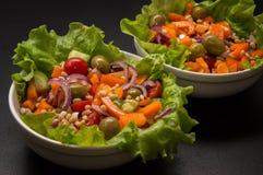 Close up. Vegan, vegetarian food. Greek salad with tofu and pine nuts. Black background