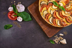 Close-up of vegetable pie. And cheese on a rustic cutting board. An Italian-American dish. Dark table. Top view Royalty Free Stock Photo