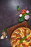 Close-up of vegetable pie. And cheese on a rustic cutting board. An Italian-American dish. Dark table. Top view Stock Images