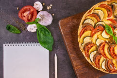 Close-up of vegetable pie and notebook. On a rustic cutting board. An Italian-American dish. Dark table. Top view Royalty Free Stock Photos