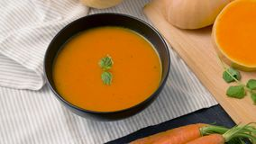 Close up of vegetable pumpkin cream soup in bowl. Food, new nordic cuisine, culinary and cooking concept - close up of vegetable pumpkin cream soup with mint stock video