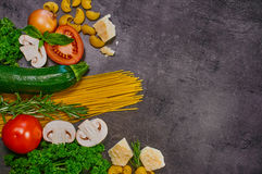 Close-up of vegetables. Cheese, spaghetti, parsley and rosemary on a dark table. Top view Royalty Free Stock Image