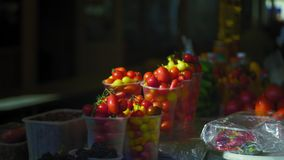 Close-Up, Vegetables In The Market Lit By The Sun`s Rays. Close-up, Vegetables in Plastic Cups in a Market Lit by the Sun`s Rays stock video
