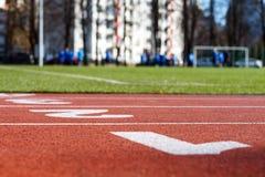 Close up vermelho da pista de atletismo no estádio, jogadores de futebol borrados Fotografia de Stock