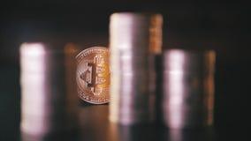 Close up vertical da vista dianteira do bitcoin dourado na pilha de moedas metálicas no fundo escuro video estoque