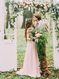 The close-up vertical photo of the groom in vintage suit kissing his bride with the big bouquet into the forehead under. The arch in the form of the white two Stock Image