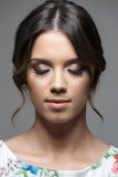 Close up vertical portrait of pretty young woman face with make up and perfect olive skin complexion. Over gray studio background royalty free stock image