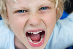 Close-up of a very angry screaming boy. Close-up portrait of a very angry screaming boy Stock Images