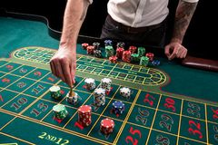 A close-up vibrant image of green casino table with roulette, with the hands of croupier and multicolored chips. A close-up vibrant image of green casino table stock images