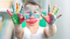 A close-up video of boy hands and fingers covered in paint
