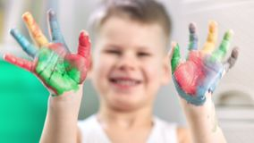 A close-up video of child hands covered in paint