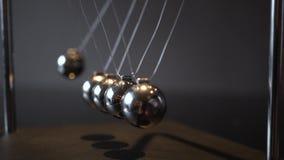 Closeup video of metal Newton cradle swining on gray background