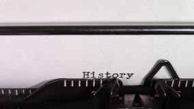 The words `History 101 ` being typed on a typewriter. A close up video of the words `History 101 ` being typed on white paper in an old manual typewriter. Shot stock footage