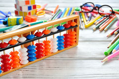 Close up view of abacus scores mental arithmetic with colorful back to school supplies over white table. Space for text. Stock Images