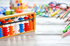 Close up view of abacus scores mental arithmetic with colorful back to school supplies over white table. Space for text. Royalty Free Stock Photo
