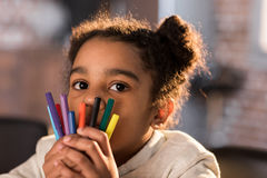 Close-up view of adorable little girl holding colorful felt tip pens and looking at camera Royalty Free Stock Photography
