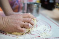 Close-up view of the adult female hands kneading dough for homemade pies. Motion blur. royalty free stock photo