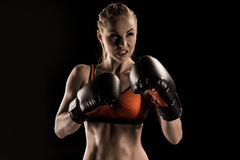 Close-up view of aggressive young sportswoman boxing in boxing gloves. Close-up view of aggressive young sportswoman boxing  in boxing gloves isolated on black Royalty Free Stock Photography
