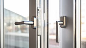 Close up view of aluminum door window handles, against a blurry. Background stock photography