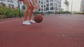 Close-up view of ambitious and focused basketball or streetball female player. She owns, controls the ball. Warm up stock video footage