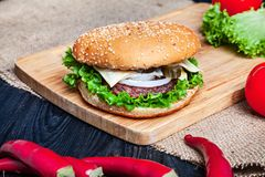 Fresh homemade burger with meat, sauce and vegetables on on wooden background. stock photos