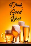 Close up view of arranged mugs of cold beer with froth and drink good beer inscription. On orange background royalty free stock photos