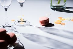 Close up view of arranged sweet macarons and empty glasses. On tabletop stock photos