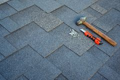 Close up view on asphalt bitumen shingles on a roof with hammer,nails and stationery knife background. stock image