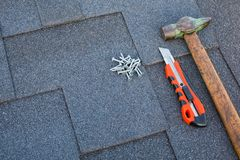 Close up view on asphalt bitumen shingles on a roof with hammer,nails and stationery knife background. royalty free stock photos