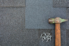Close up view on Asphalt Roofing Shingles Background. Roof Shingles - Roofing. Asphalt Roofing Shingles Hammer and Nails Royalty Free Stock Photo