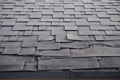 Close up view on Asphalt Roofing Shingles roof damage covered with frost. stock image