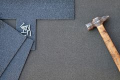 Close up view on asphalt shingles on a roof  with hammer and nails background Royalty Free Stock Photo