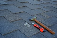 Close up view on asphalt shingles on a roof with hammer,nails and stationery knife background royalty free stock photo