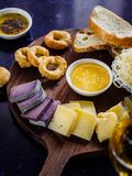 Close up view of assorted cheese types sauce and bread on wooden. Cutting board stock photo