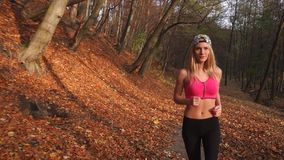 Close-up view of the attractive blonde woman jogging along the autumn park. Close-up view of the attractive blonde woman jogging along the autumn park