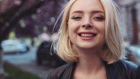 Close up view of attractive blue-eyed blonde girl with natural makeup happily smiling to camera. Sakura, cherry blossom stock video footage
