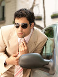Businessman grooming on car mirror. Royalty Free Stock Photos