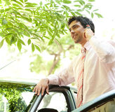 Businessman on phone call. Close up view of an attractive businessman with his car having a phone conversation using a hands free set in a tree lined street in Royalty Free Stock Image