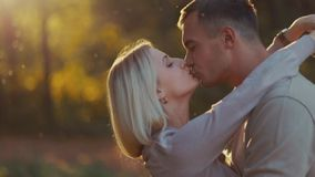 Close up view of attractive young blonde girl passionately kissing her handsome boyfriend in a warm autumn sunshine stock footage