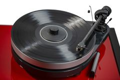 Close up view of audio record player with black vinyl disk on red surface isolated. Beautiful backgrounds royalty free stock image