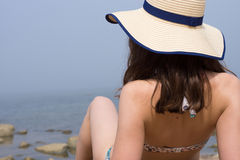 Close up view of a back of brunette woman wearing swimming suit and straw hat, sitting near water on sand and looking to sea. Stock Image