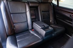 Close-up view in the back inside the interior of the car, comfortable passenger seats from black genuine leather and modern royalty free stock photography