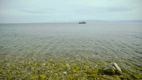 Close up view of Baikal lake. Turquoise water and rocky coast underwater. Ship on the horizon stock footage