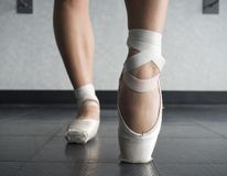 Close up view of a ballerina ballet dance, warming up her feet in ballet class. With focus on her foot in her pointe shoe ballet slipper en pointe on the block stock photography