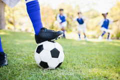 Close up view of balloon under football boots against children playing background Royalty Free Stock Image