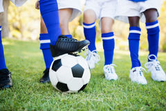 Close up view of balloon under football boots with children playing Stock Image