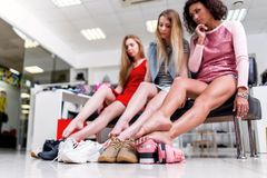 Close-up view of barefoot long slim female legs surrounded by variety of sports shoes. Three female friends sitting stock photography